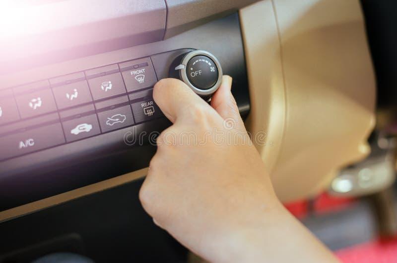 打开汽车空调系统,在仪表板的按钮的人的手在汽车 免版税库存图片