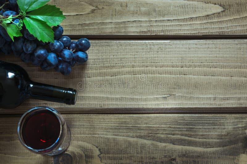 打开瓶与一个玻璃、拔塞螺旋和成熟葡萄的红葡萄酒在一个木板 复制空间和顶视图 图库摄影