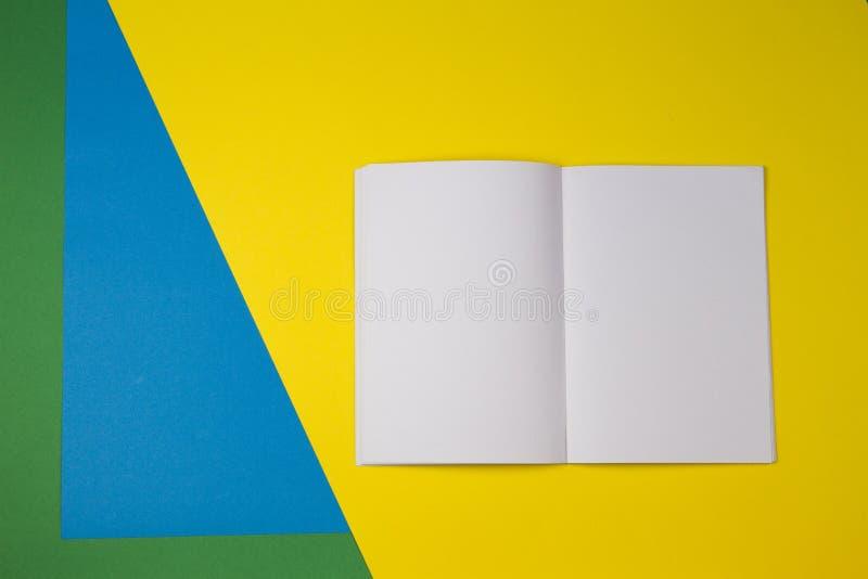 打开白纸笔记本有黄色,蓝色和绿色背景 图库摄影