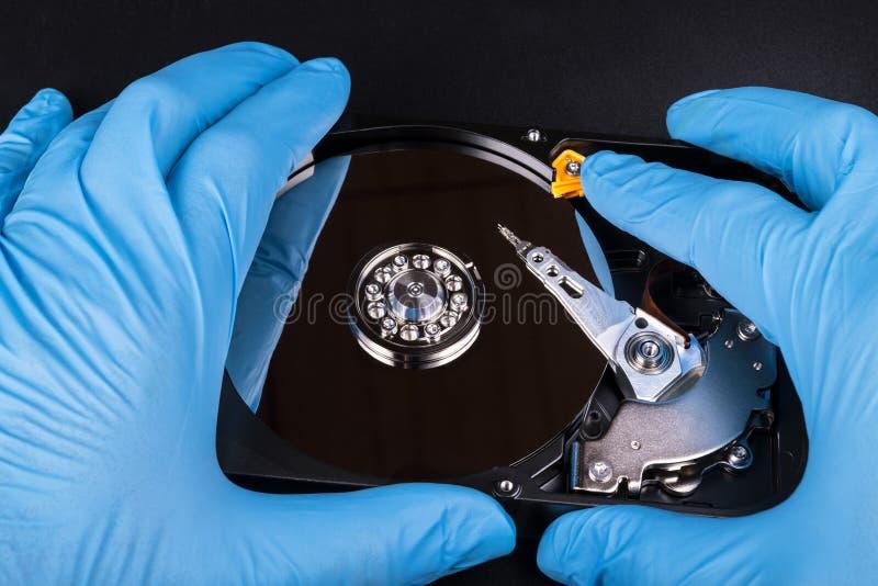 打开硬盘驱动器在蓝色手套的手上 库存图片