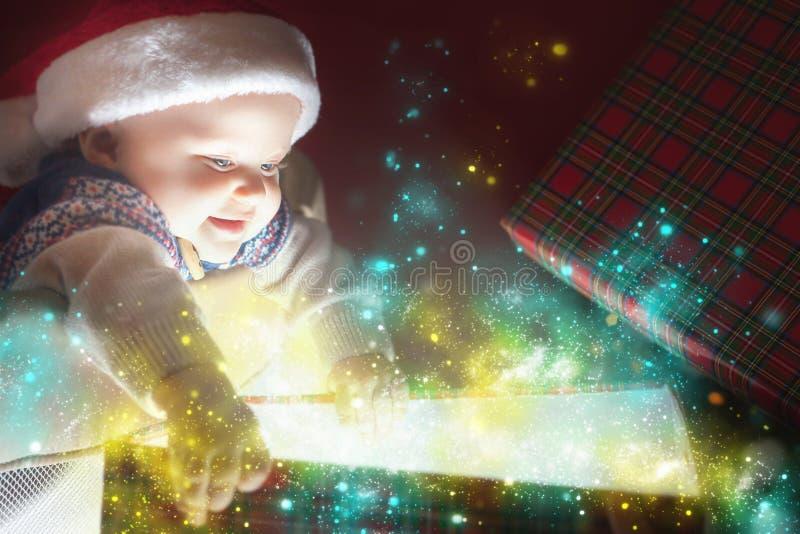打开礼物或礼物盒的圣诞节婴孩 库存图片