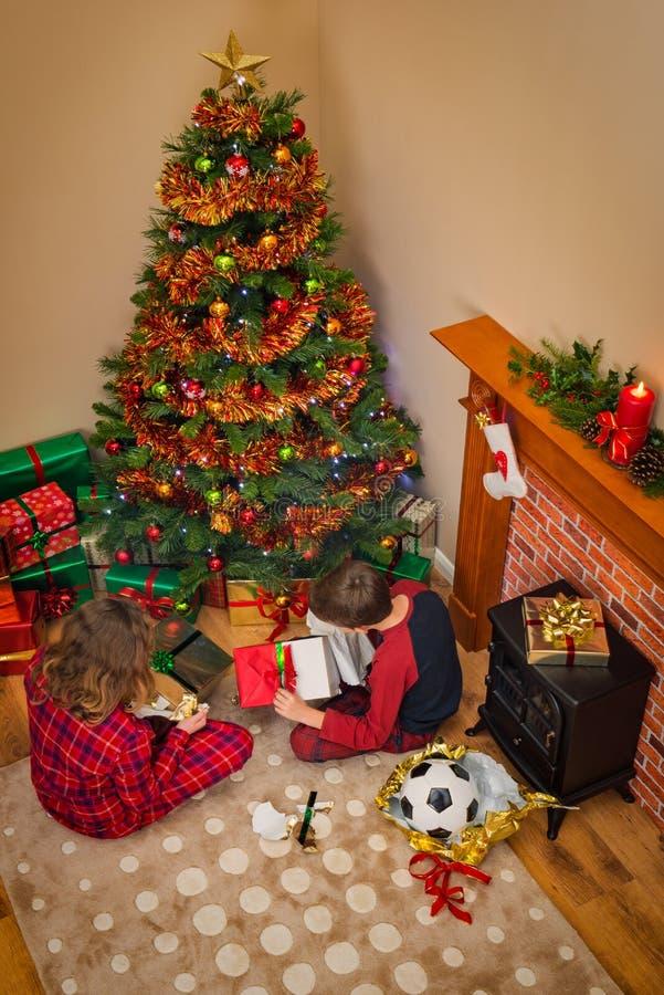 打开礼物的孩子在圣诞节早晨 免版税库存图片