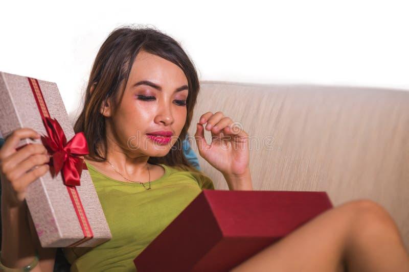 打开礼物盒的年轻美好和愉快的亚洲印度尼西亚妇女藏品生日或圣诞礼物快乐和激动 免版税库存照片