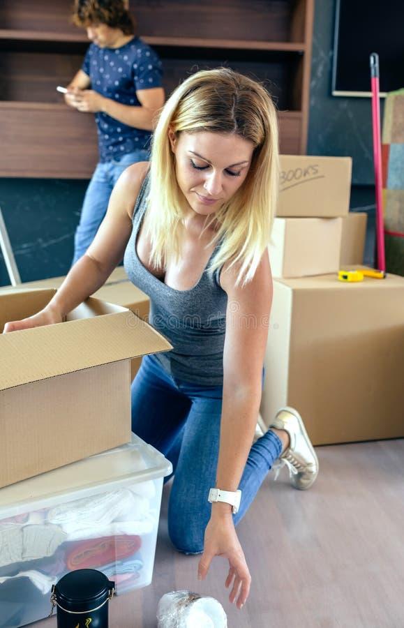 打开移动的箱子的妇女 免版税库存照片