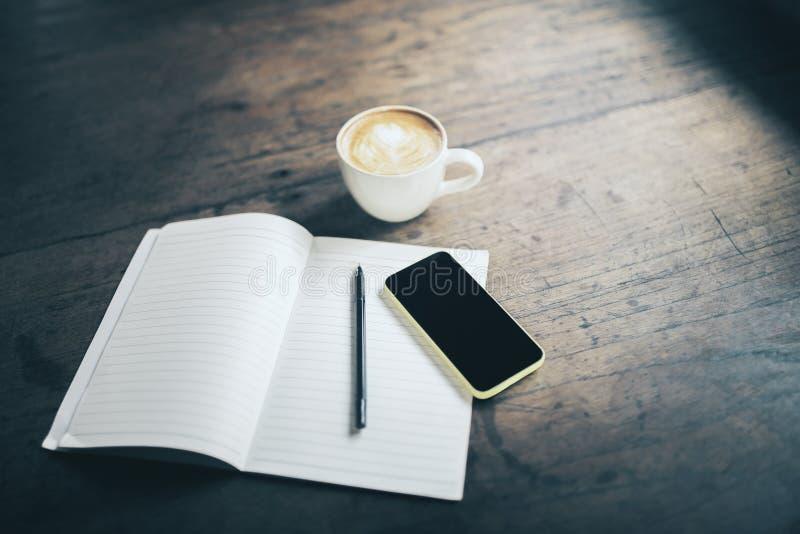打开空白的笔记本、笔、手机和咖啡在木的 免版税图库摄影