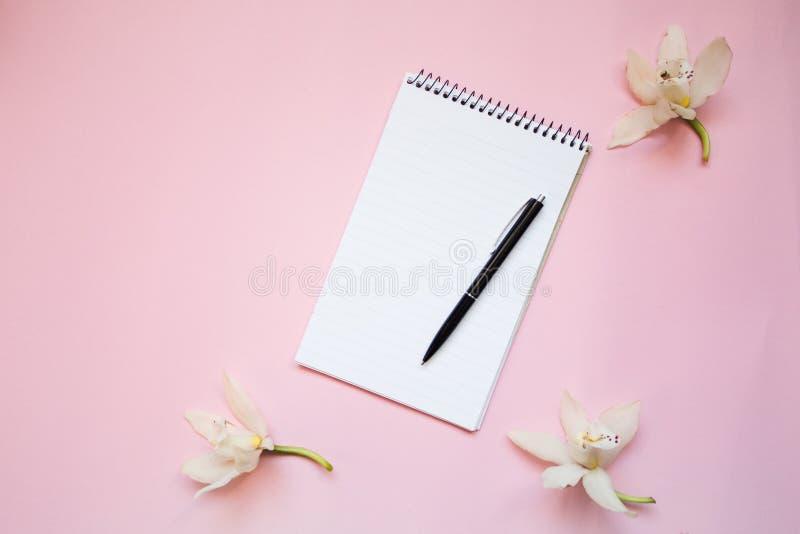 打开空白的笔记本,在桃红色背景的花 文本的,顶视图空间 免版税库存照片