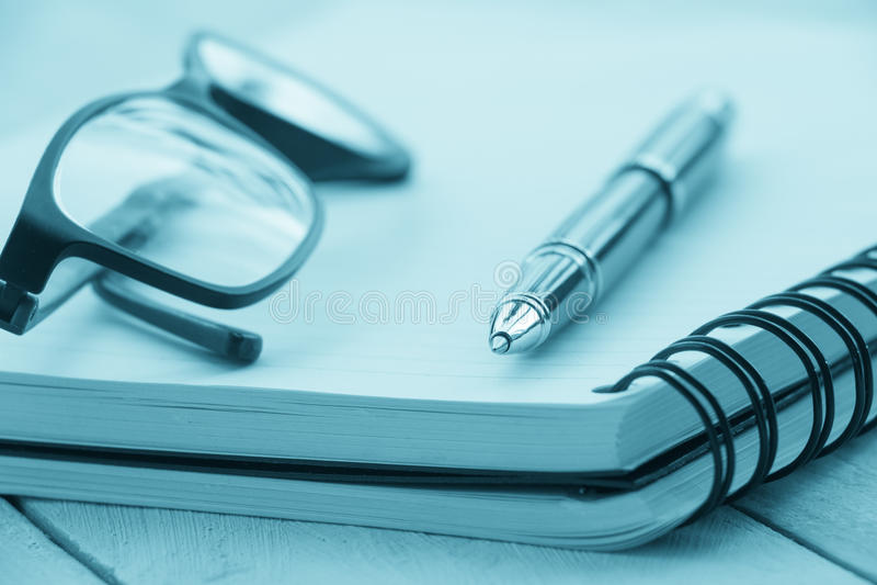 打开空白的笔记本,在背景的笔镜片 库存图片