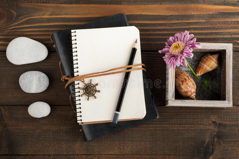 打开空白的笔记本,小卵石,壳,花 免版税库存图片