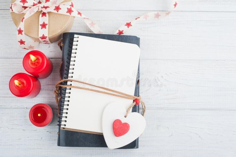 打开空白的计划者,有被点燃的蜡烛和红色心脏的 免版税库存照片