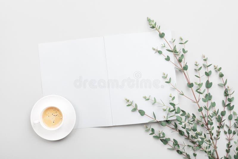 打开空的笔记本、咖啡和在灰色台式视图的玉树叶子 Minimalistic运转的书桌 平的位置 库存照片