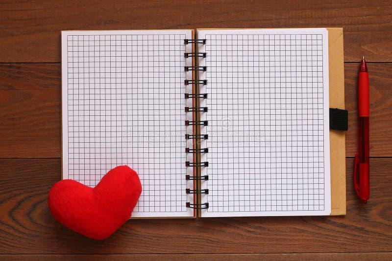 打开笔记本和笔和红色长毛绒心脏在一张木桌上 免版税图库摄影