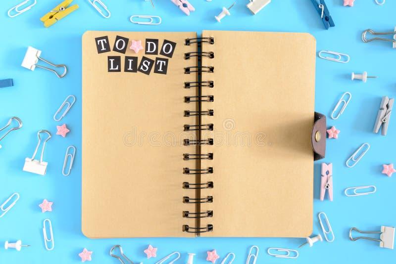 打开笔记本在文具混乱的中心  要做在棕色页的名单的题字 夹子,晒衣夹和 免版税图库摄影