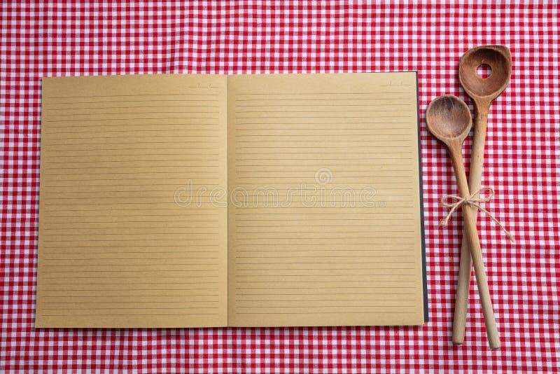 打开笔记本,在红色桌布,顶视图,拷贝空间的木厨房器物 库存图片