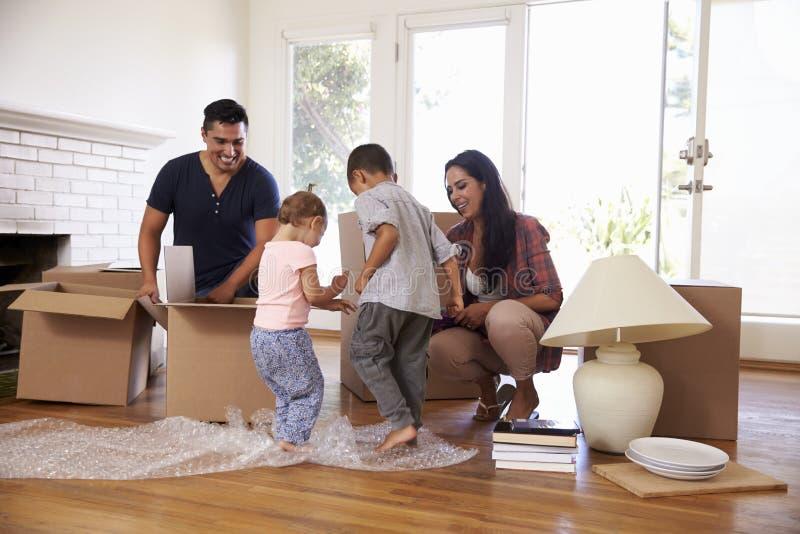 打开箱子的家庭在新的家在移动的天 免版税库存图片