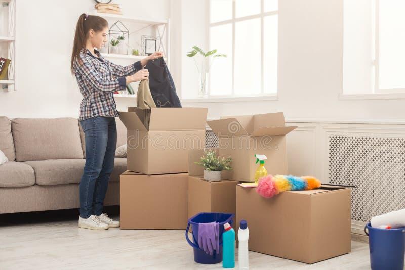 打开箱子的少妇在移动以后 免版税库存照片