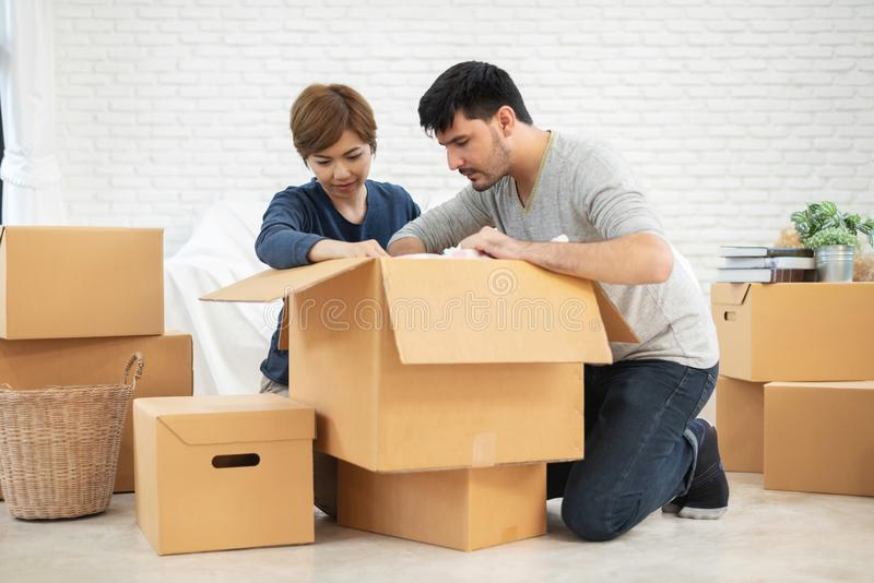 打开纸板箱的夫妇在新的家 房子移动 免版税库存照片