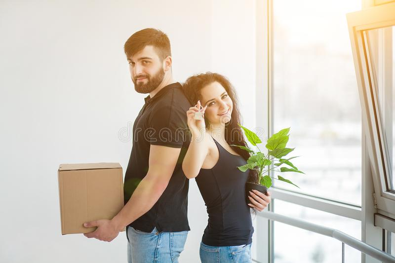打开纸板箱的年轻夫妇在新的家 房子移动 库存照片