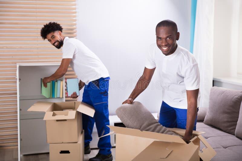 打开纸板箱的搬家工人在家 免版税库存图片