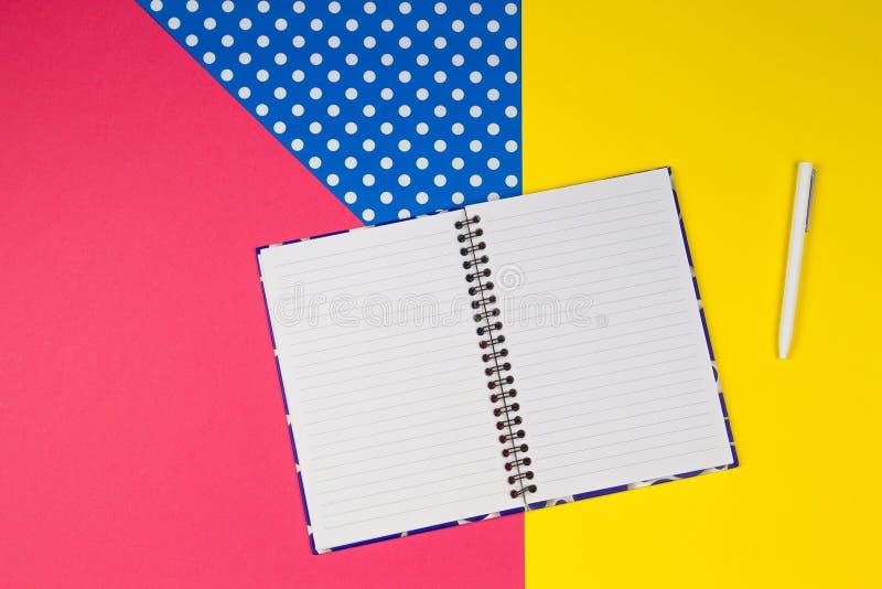打开纸笔记本和白色笔在五颜六色的背景 图库摄影