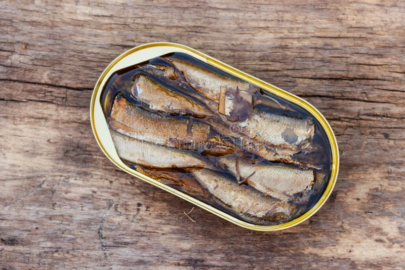 打开西鲱锡罐在土气木桌上的 免版税图库摄影