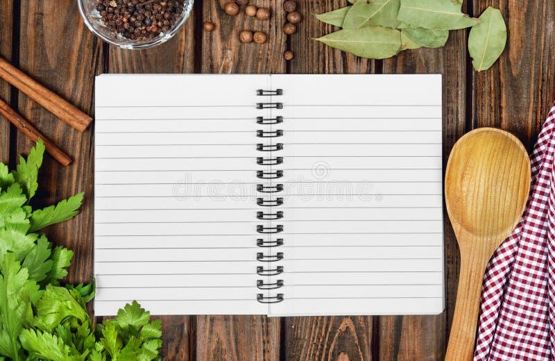 打开食谱书用新鲜的草本和香料 免版税库存照片