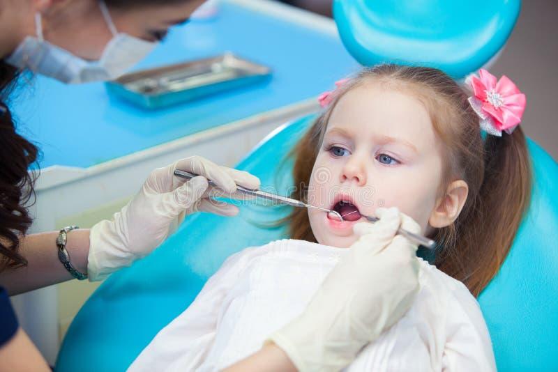 打开他的相当小女孩特写镜头嘴宽在口腔的检查时在牙医 库存图片