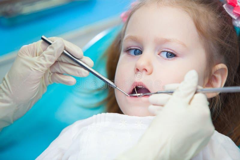 打开他的相当小女孩特写镜头嘴宽在口腔的检查时在牙医 免版税库存照片