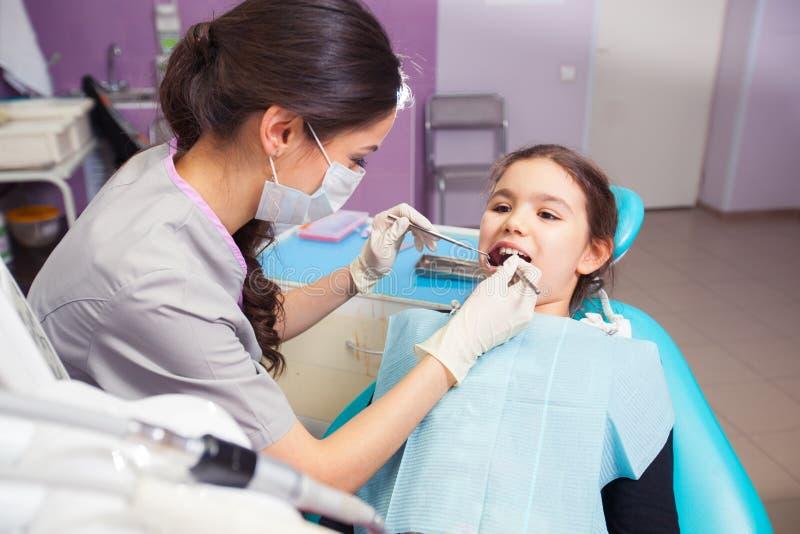 打开他的相当小女孩特写镜头嘴宽在对待她的牙期间由牙医 免版税图库摄影