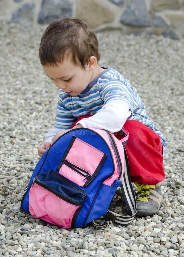 打开他的袋子的孩子 免版税库存图片