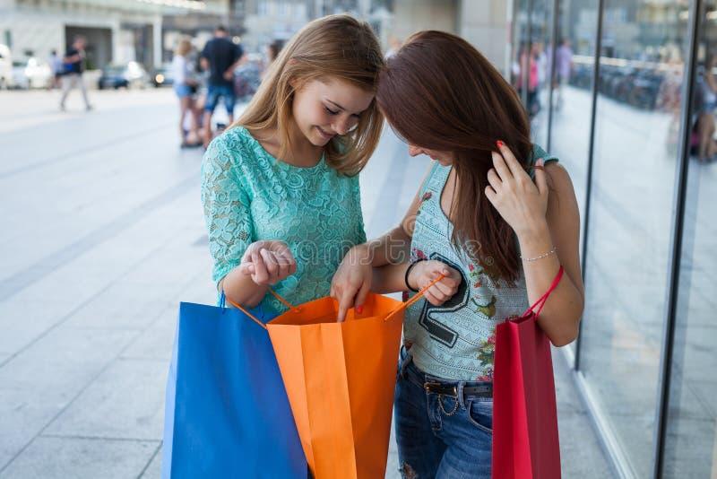 打开他们的购物袋的女孩 销售的季节 免版税库存图片