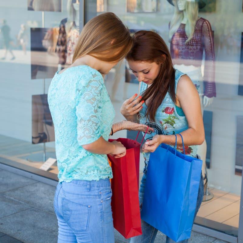 打开他们的购物袋的女孩 销售的季节 库存图片