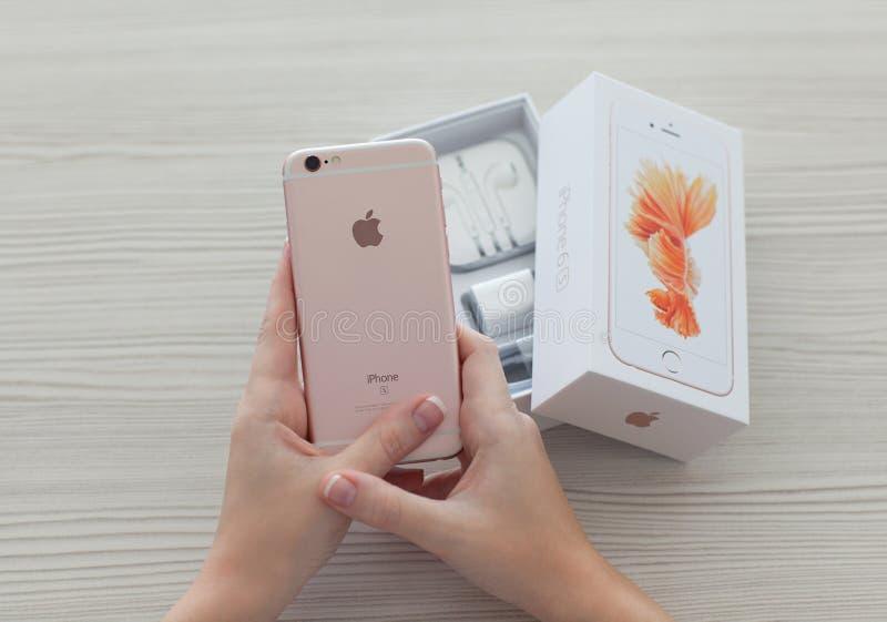 打开iPhone6S罗斯金子的妇女手 免版税库存照片