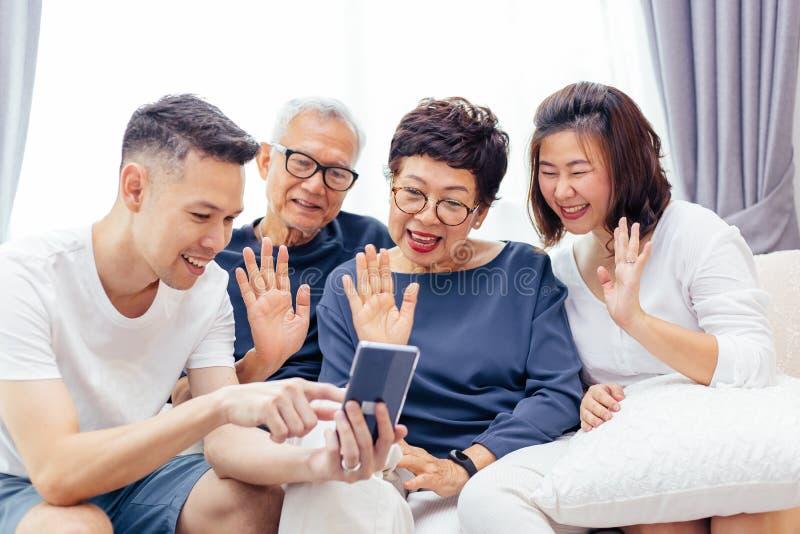 打录影电话和挥动在访问者的大家庭 与一起资深和年轻夫妇的亚洲多一代家庭 免版税库存图片