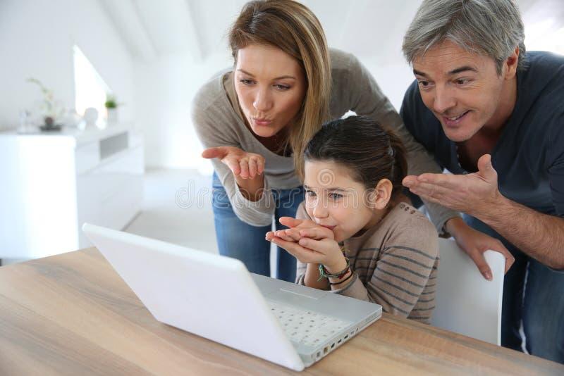 打录影电话的家庭在膝上型计算机 图库摄影