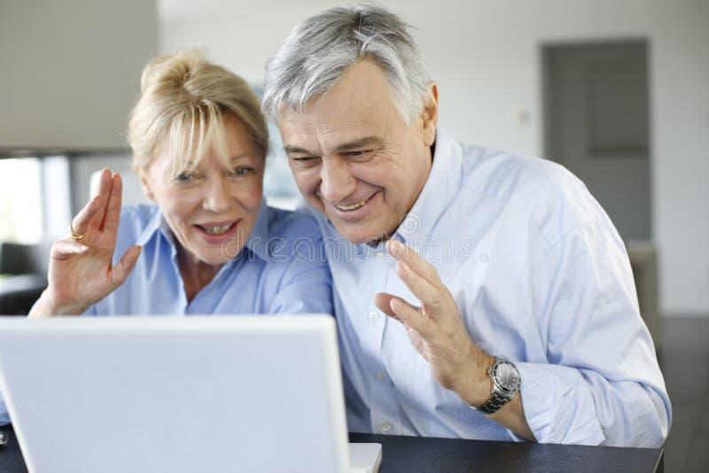 打录影电话的现代资深夫妇在膝上型计算机 免版税库存照片