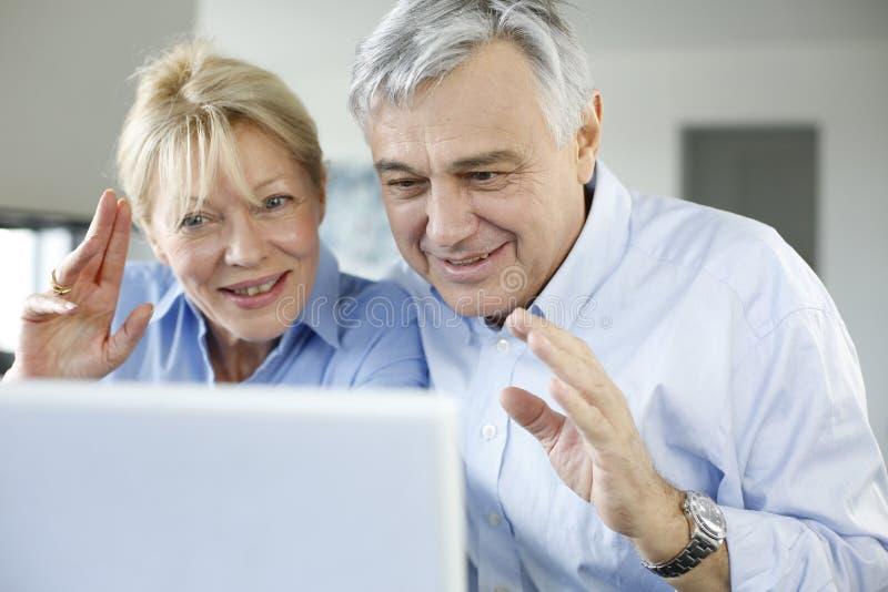 打录影电话的资深夫妇在互联网 库存图片