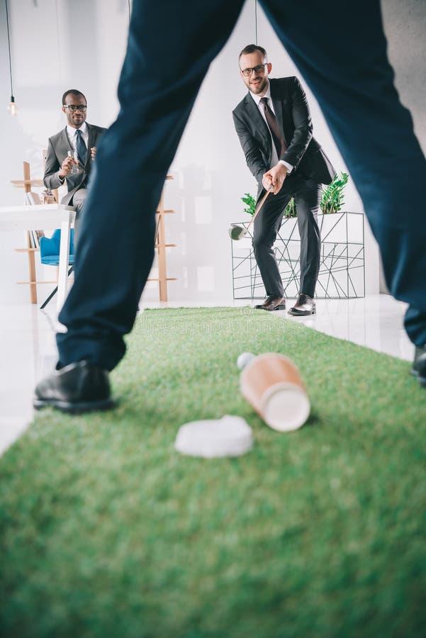 打微型高尔夫球的不同种族的小组商人 免版税库存照片