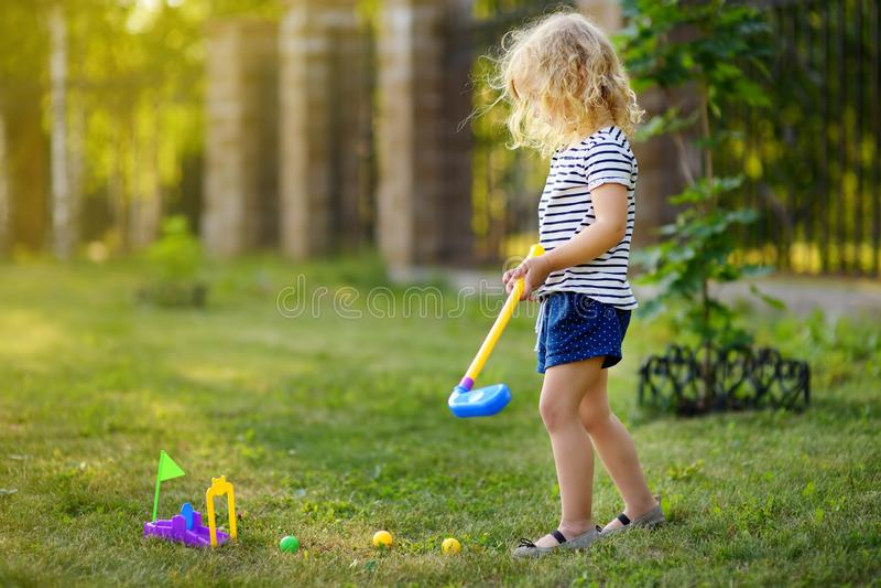打微型高尔夫球的女孩在春天公园 获得的孩子与活跃休闲的乐趣在度假 库存图片