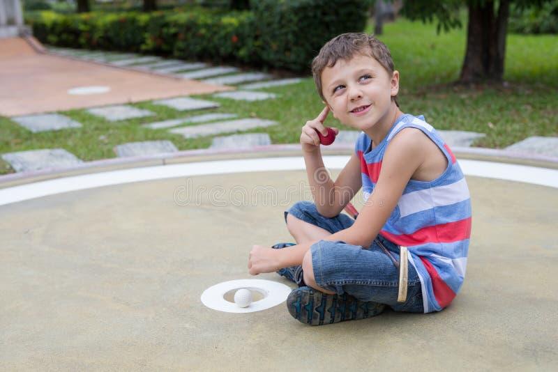 打微型高尔夫球的愉快的小男孩打微型高尔夫球 库存照片