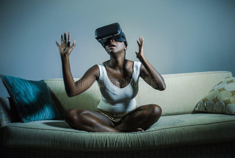 打惊奇和惊奇的虚拟现实电子游戏的年轻可爱的黑人美国黑人的妇女佩带VR风镜 免版税库存图片