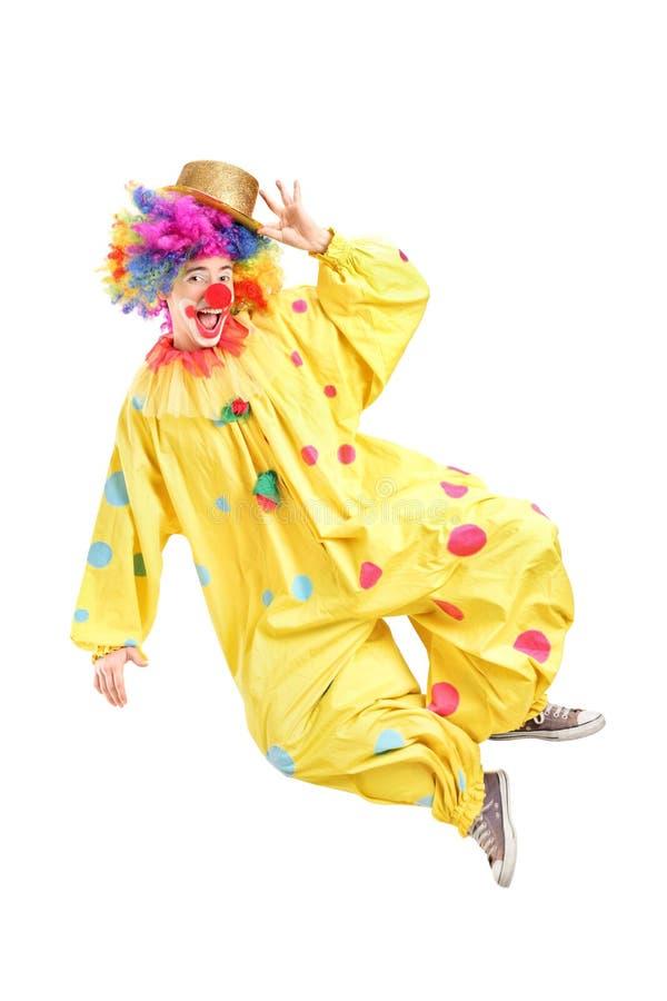 打手势一个男性的小丑的全长画象跳跃和 图库摄影
