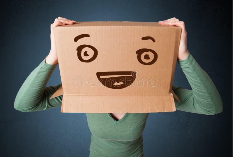 打手势与在她的头的一个纸板箱的少妇有smil的 库存图片