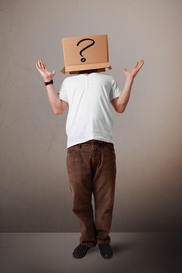 打手势与在他的头的一个纸板箱的年轻人有questi的 免版税图库摄影