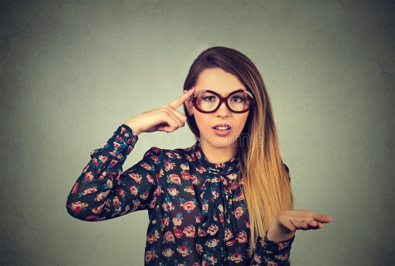 打手势与她的手指的恼怒的妇女反对寺庙要求是您疯狂? 免版税图库摄影