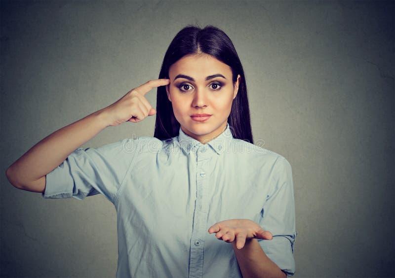 打手势与手指的恼怒的妇女反对寺庙是您疯狂? 免版税库存照片