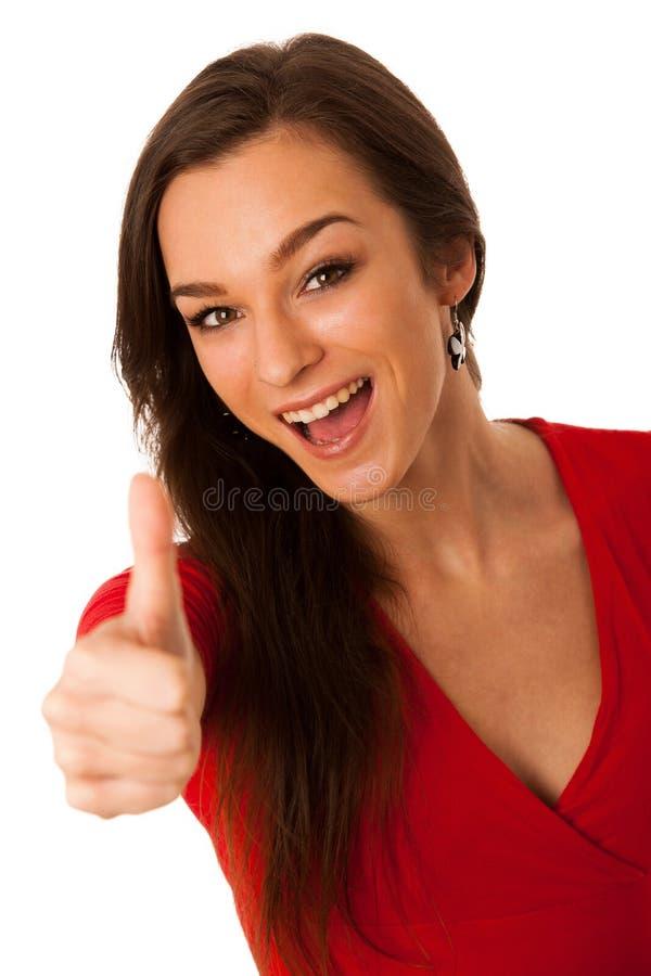 打手势与显示的美丽的女商人赞许的成功 免版税库存照片