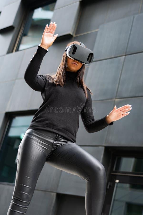 打手势与虚拟现实玻璃的被聚焦的年轻女人在未来派城市 免版税库存图片