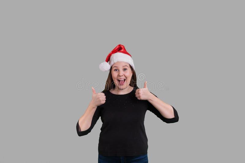 打手势两赞许的年轻的夫人戴圣诞节假日圣诞老人项目帽子 库存照片