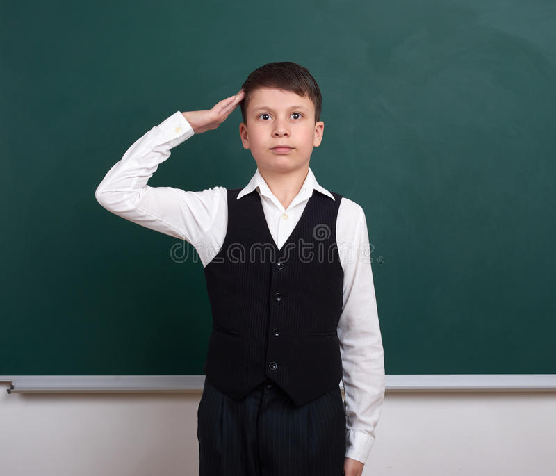 打手势军事致敬,在绿色空白的黑板背景附近的画象的男生,在经典衣服,一个学生, educa穿戴了 免版税库存照片