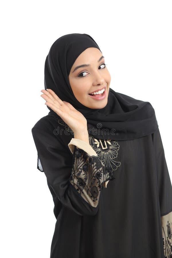 打手势听用在耳朵的一只手的阿拉伯沙特酋长管辖区妇女 免版税库存图片
